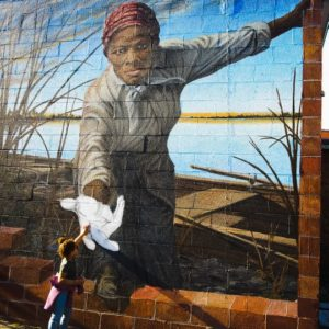 """A photo captured by Tracy Lynndee in Cambridge, Maryland of her 3-year-old granddaughter, """"Lovie"""" Hope Duncan touching the hand of abolitionist Harriet Tubman has become a viral sensation on the internet. (Photo: Tracy Lynndee/Special to the Democrat)"""