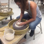 Marissa Sowinski demonstrates wheel throwing techniques during her final project